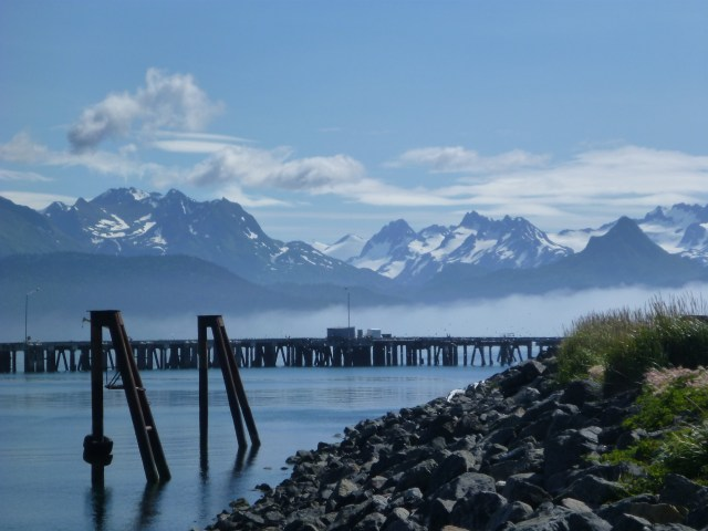 The pier and pilings surrounding the Homer, Alaska boat harbor. There are rocks on the jetty in the foreground and tall snow capped mountains across the bay. It's sunny and there are a few clouds and fog in places on the surface of the water.