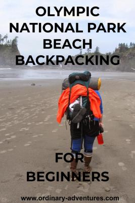 A person wearing rubber boots walks down the beach with a large backpack. The backpack holds a tent and an orange rain jacket. In the distance are cliffs and trees surrounding the beach.
