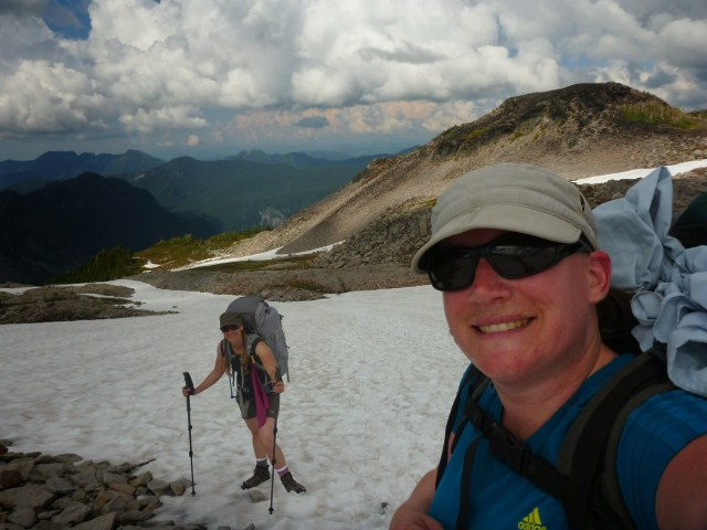 Two backpackers climbing a rocky snowfield