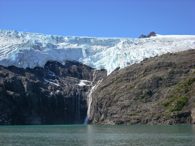 A hanging glacier has a waterfall coming down to the water on a wildlife and glacier cruise from Whittier Alaska