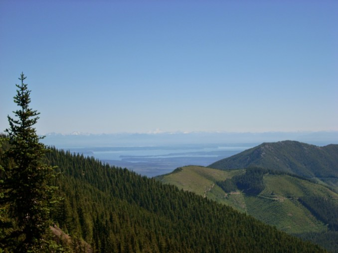 View from the Mt Townsend trail includes a forested hillside, a distant islands and waterways and beyond that, distant mountains