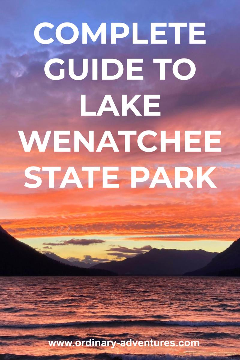A sunset behind mountains along a large alpine lake. Text reads: Complete Guide to lake wenatchee state park