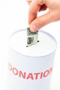Hand donating money to charity