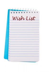 A notepad with wish list written on it isolated on a white background, christmas wish list