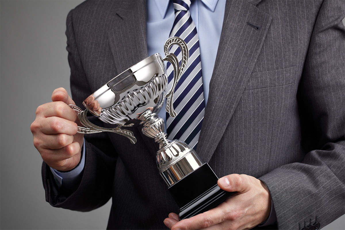 Image of man holding an award