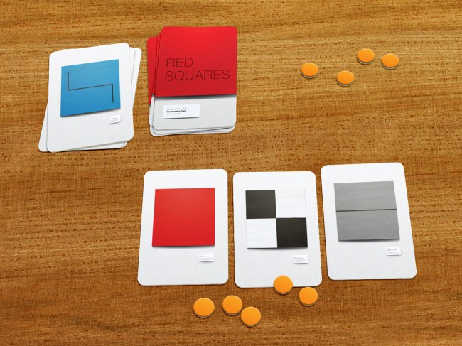 Custom playing cards set out on a table with piles of round tokens used for currency.