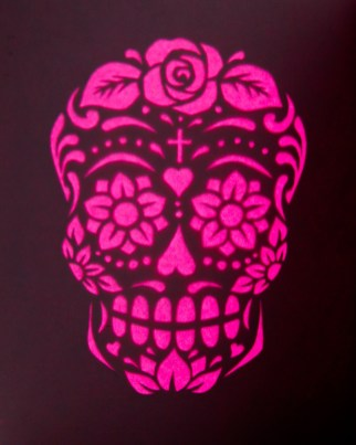A backlit calavera design cut out of card, with a flourescent pink backing, consisting of flowers, hearts and swirls silhouetted against the darkness