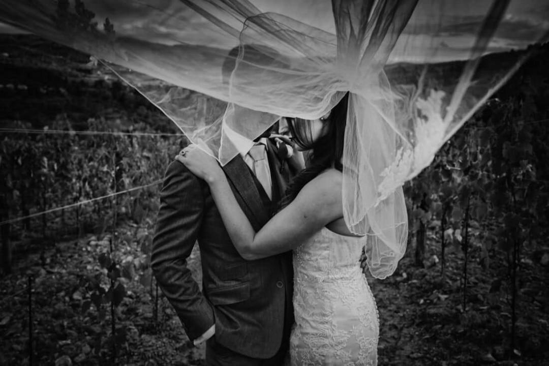 Jane & Aimun kiss in the vineyard