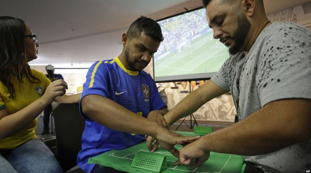 Carlos Junior (in blue) takes the help from interpreter Helio Fonseca de Araujo (R) during the Brazil versus Mexico match, Monday