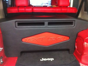 """Two MMats Pro Audio Monster 12"""" subwoofers installed in a custom box in a four door Jeep Wrangler."""