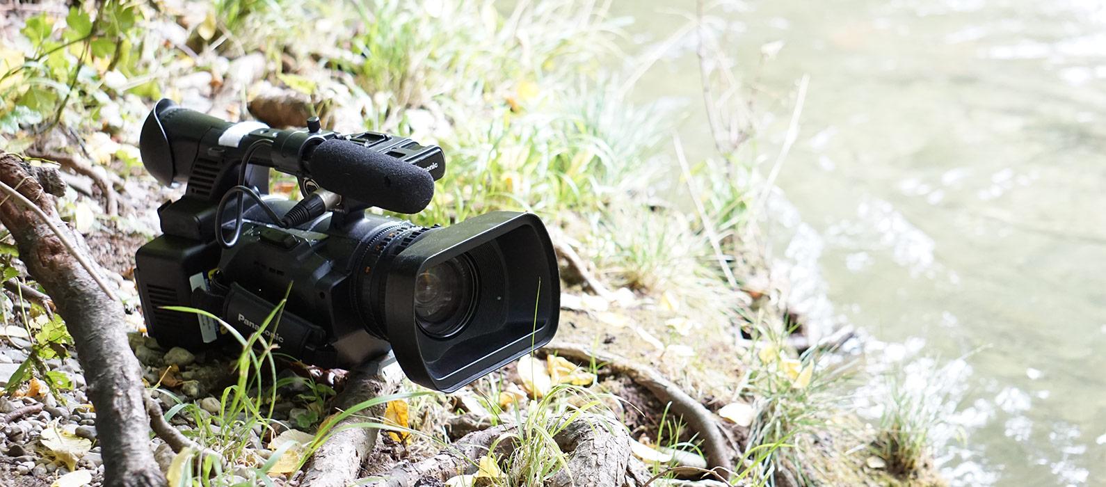 Hier ist eine Kamera auf einer Wiese zu sehen. Die schwarze Kamera ist nicht ganz auf dem Bild. Sie ragt von links schräg nach vorne ins Bild. Rundherum befinden sich einige Äste, Blätter und ansonsten ist eine Wiese zu sehen.
