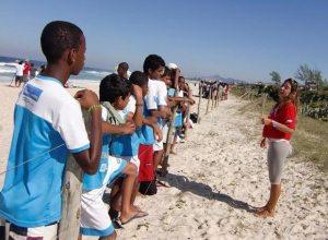 A bióloga Beatriz Vanacôr em atividade na praia de Itaúna, dando aula de Educação Ambiental sobre a restinga