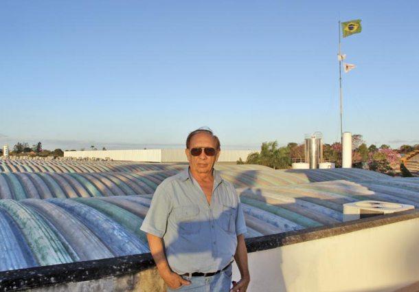Ernesto no terraço da fábrica em Araruama, cercada de árvores nativas, ipês, palmeiras e  frutíferas.