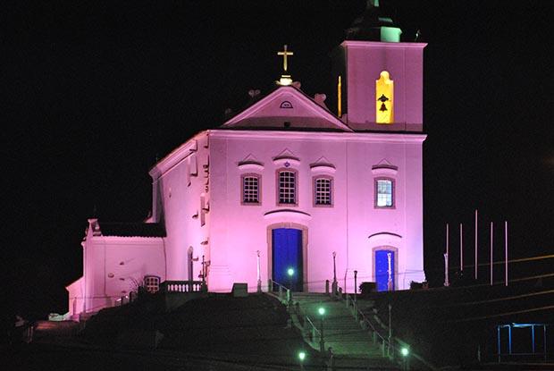 A igreja de N. Sra. de Nazareth iluminada com o cor-de-rosa da campanha (Foto: Arquivo Jornal O Saquá)