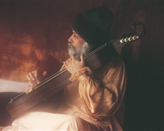 Osho playing an instrument