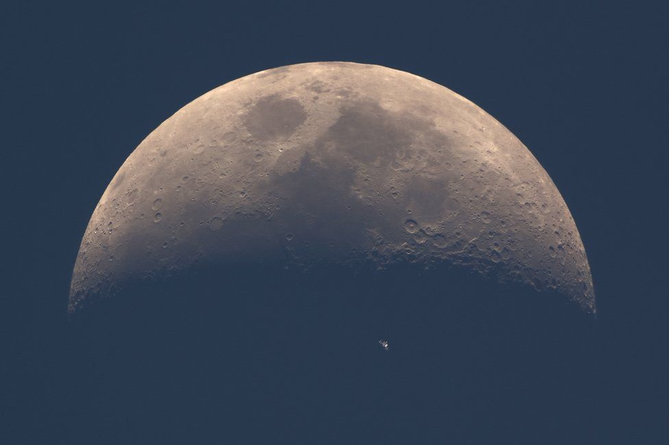 The International Space Station moves across the face of the Earth's natural satellite, the Moon