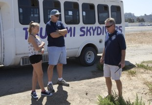 Waiting in the landing zone Lauren,13 and Randy Scott talk with Rich Grimm, owner of Tsunami Skydiving in Oceanside, which donated the tandem jump for Carrie Scott
