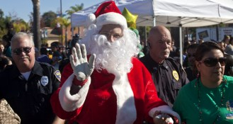 Santa is escorted by security through the crowd.