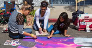 Raziah Roushan (center) creating with chalk at the  Oceanside Days of Art
