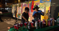 George Antonio and Ethan Lopez choose their next colors for their contribution to the Combat Arts community mural