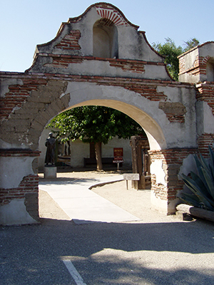 An aging archway at Mission San Miguel, perched half way between Mission San Antonio and San Luis Obispo, frames a statue of Franciscan Fr. Junipero Serra, the founder of California's chain of missions. photo by: Cecil Scaglione