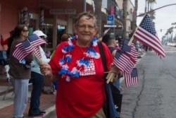 Chris Gow, 2016 Parade Grand Marshal and one of the many volunteers handing out flags donated by Friends of Oceanside Parks at last years parade.