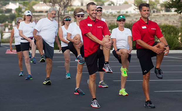 Trainers Paul Carey and Cody lead some of the Lucky 13 in stretching exercises