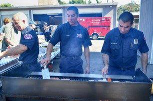 Oceanside Firefughters Mike Presti, Jacob Goran and Matt Murguia prepare food after the ceremony