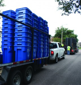 Brand new gray and blue carts are delivered to customers as the County's 2-1-1 automated  garbage collection service is poised to begin at the end of the month.