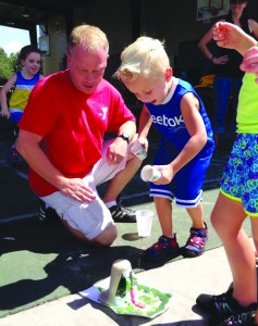 Mr. Rob the counselor and Bradley Clark, 4, watch as a volcano erupts.