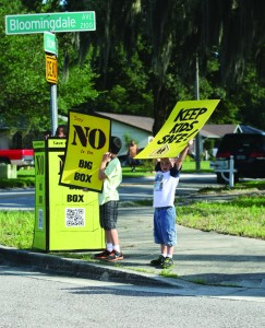 Children hold up signs during a community rally last year opposing the planned Big Box devel-opment on Bloomingdale Ave. Residents are now gearing up for another meeting hosted by the County involving the issue.