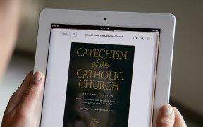 WOMAN DISPLAYS E-BOOK VERSION OF CATHOLIC CATECHISM