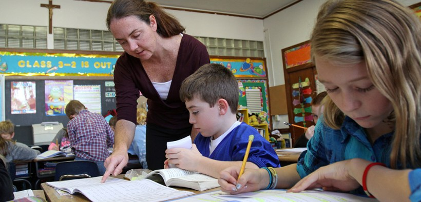 TEACHER WORKS WITH STUDENTS AT CATHOLIC SCHOOL IN NEW YORK