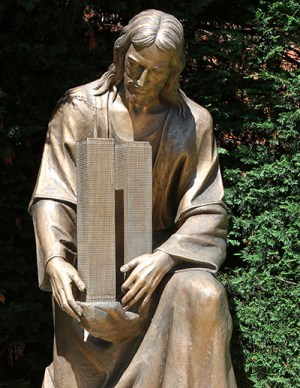 A sculpture of Jesus embracing the twin towers