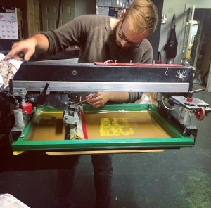 Production Manager Jake Behr prepares the printing press before starting to print a new T-shirt.  Photo provided by Zink Screenprinting and Design