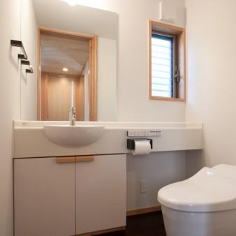 9:1階トイレ 将来の身体的変化にも対応出来るよう、必要な機能をゆったりと配置している。手洗い器の下の扉の引き手はL型に加工したタモの無垢材を付けただけ。