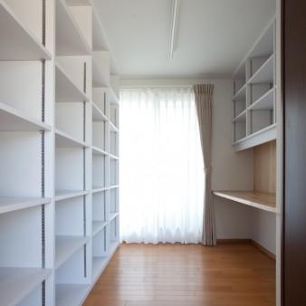 12:図書室 建て主が長年収集してきた書物を収納するだけではなく、書斎の機能そして家事を行う機能も併せ持つ。