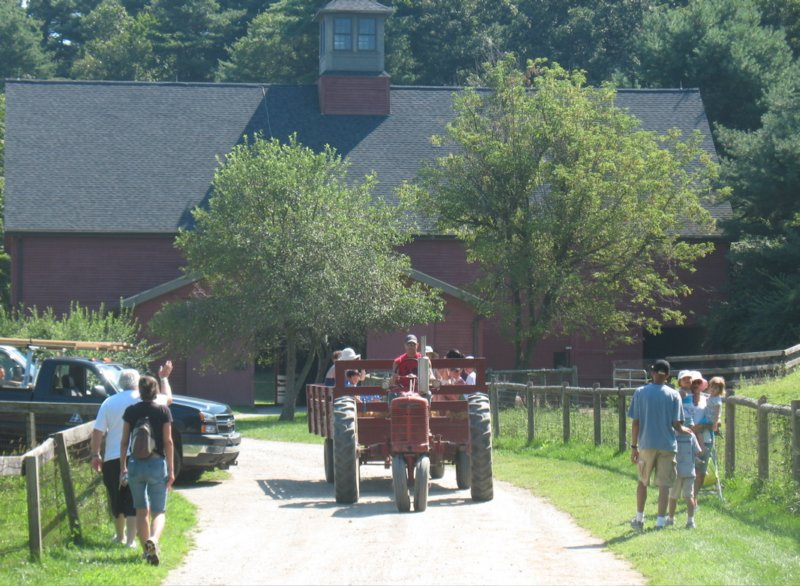 The tractor pulls the hayride in front of the big red barn.