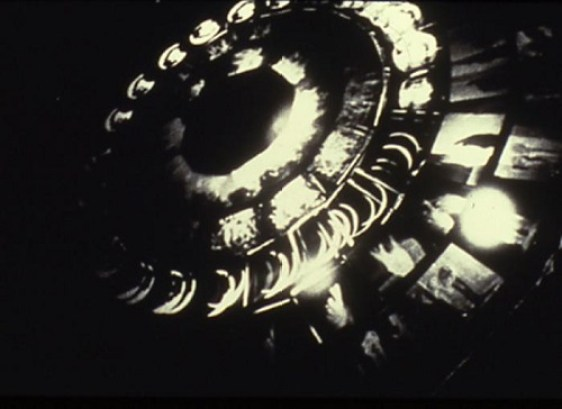 Retrospectroscope (1996) by Kerry Laitala, plexiglass disc with silver gelatin transparencies on rotating motor, 5' diameter disk x 4' height.