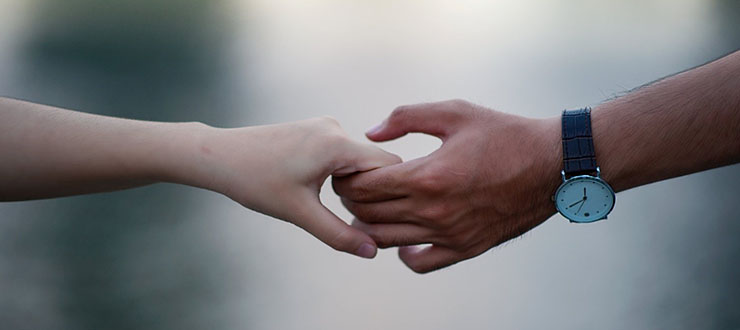 A male and a female hands holding each others
