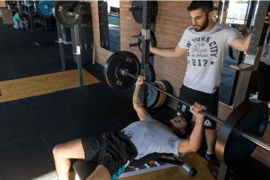 a man lifting weight and a trainer