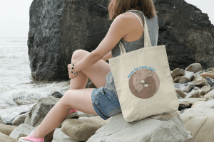 Made For Each Otter tote bag mockup featuring a young woman sitting on a rock by the sea.
