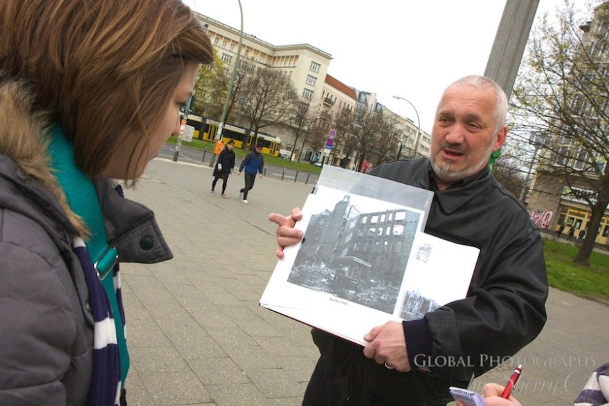 Tour leader showing old photos of Berlin during cold war
