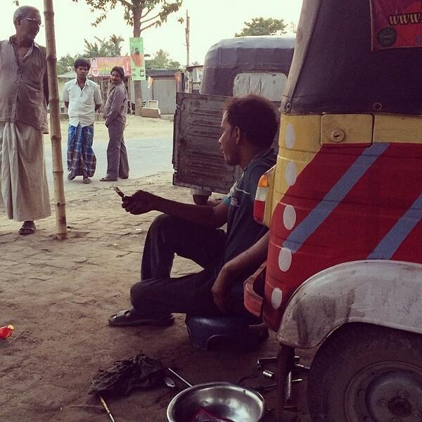 Indian mechanic eats ice cream as he repairs Rickshaw