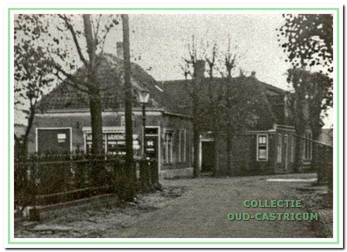 Links de winkel van Anton Liefting. De woning daarachter werd bewoond door Maartje Jannes. Links vooraan is nog het ijzeren hek zichtbaar van het Armenhuis met op de hoek nog een oude gaslantaarn.