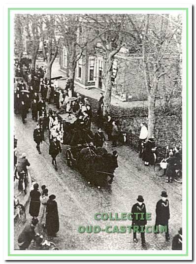 De begrafenisstoet van burgemeester Lommen ter hoogte van het raadhuis in de Dorpsstraat. Rechts Huize Kerkzicht.