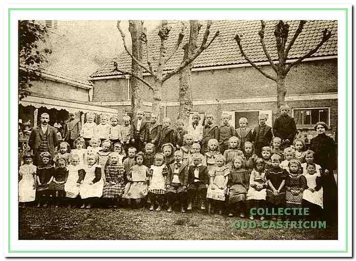 Schoolhoofd Bussen en een onbekende onderwijzeres met de kinderen op de binnenplaats van de openbare lagere school naast het gemeentehuis.