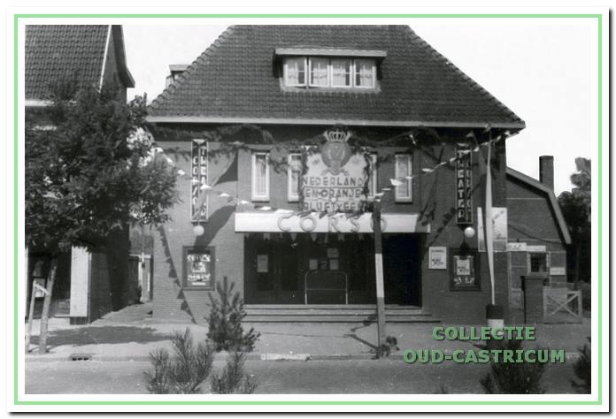 """31 augustus 1945 Koninginnedag: Versierde Corso theater tijdens de bevrijdingsfeesten. De tekst die op het bord staat luidt:""""Nederland en Oranje blijft 1."""""""