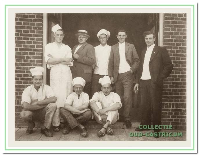 Omstreeks 1930. Hendrik Hemmer (met strohoed) en personeel in de deuropening van zijn bakkerij aan de Ruiterweg. Rechts zijn zoon Gerard, die hem later zou opvolgen.