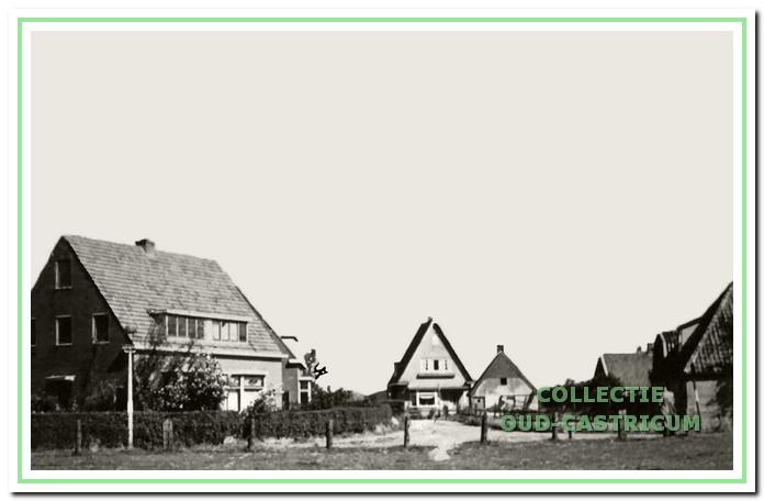Foto genomen over de tweede ingang. Links twee nieuwe dubbele woonhuizen (nr 9), waarin o.a. de families Van Essen, Scheerman, Harms en Nijsen woonden. Achtereenvolgens naar rechts het huis van houthandelaar Jo Duin (nr 15), het huisje van Jan Zonneveld (nr 10) en van Simon Dekker (nr 14). Uiterst rechts stond aan de Stetweg de boerderij van de familie van den Berg.